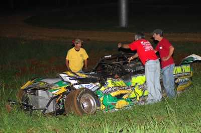 Workers check on Chris Wall's mangled machine. (Sherry Kiser)
