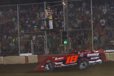 Shannon Babb takes the checkers after a hard-fought Summernationals race. (Jim DenHamer)