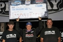 Darrell Lanigan holds his $10,000 winner's check aloft while flanked by crewmen Adam Logan (left) and Richie Davis (right) following his 13th World of Outlaws Late Model Series win of 2014 at Merritt Speedway in Lake City, Mich. (Jim DenHamer)