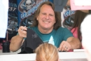 Scott Bloomquist signs autographs at his t-shirt trailer before the start of Saturday night's USA Nationals finale at Cedar Lake Speedway in New Richmond, Wis. (Bruce Nuttleman)