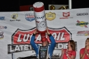 Scott Bloomquist pretends to take a celebratory swig from an oversized bottle after winning the Lucas Oil Late Model Dirt Series Budweiser 50 on April 29 at Tri-City Speedway in Granite City, Ill. (heathlawsonphotos.com)